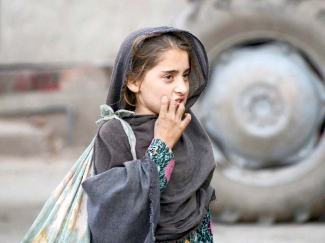 An Afghan girl works at a fruit market in the Badami Bagh area of the city. PHOTO: ONLINE