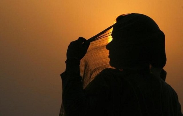 a-woman-adjusts-her-scarf-as-the-sun-sets-over-kashmirs-dal-lake-in-srinagar-4-2