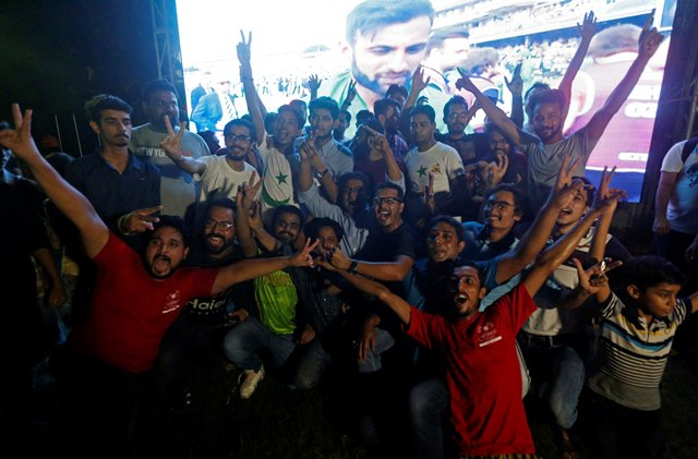 Jubilant: Cricket fans, in Karachi, celebrate in front of a screen after Pakistan defeated India in the ICC Champions Trophy finals. PHOTO: REUTERS