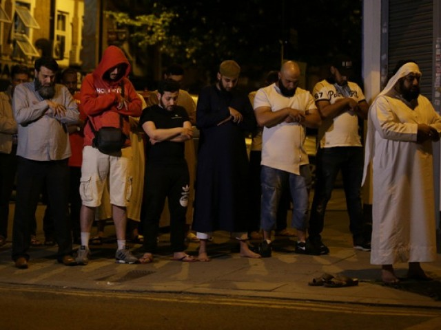 Muslims pray on a sidewalk in the Finsbury Park area of north London after a vehichle hit pedestrians, on June 19, 2017.  One person has been arrested after a vehicle hit pedestrians in north London, injuring several people, police said Monday, as Muslim leaders said worshippers were mown down after leaving a mosque PHOTO: AFP