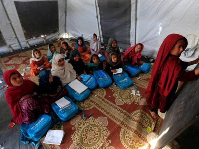 Afghan refugee children attend a class at a refugee camp. PHOTO: REUTERS