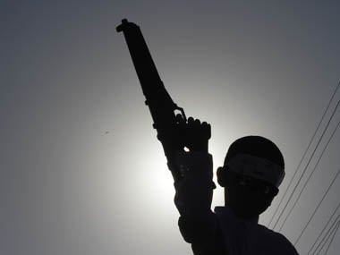 a-boy-is-silhouetted-against-the-sun-as-he-holds-a-toy-gun-during-a-rally-in-karahi