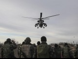 russian-army-mi-35-military-helicopter-patrols-the-area-as-ukrainian-servicemen-guard-a-checkpoint-near-the-village-of-strelkovo