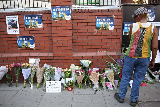 A man looks at floral tributes left close to the scene of a van attack in Finsbury Park, north London. PHOTO: AFP