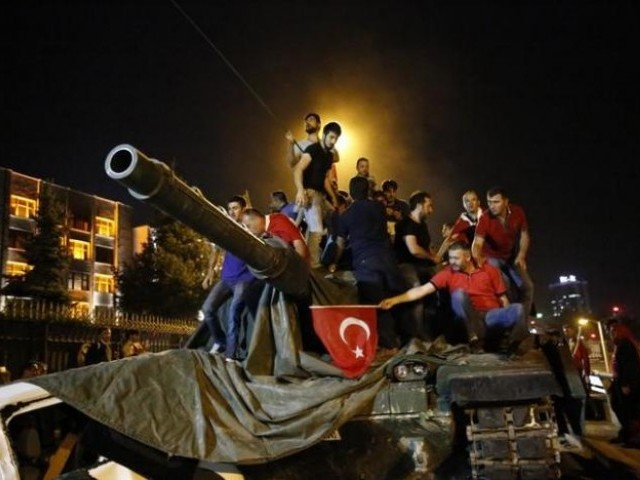 People stand on a Turkish army tank in Ankara, Turkey July 16, 2016. PHOTO: REUTERS