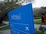 an-employee-walks-past-a-signage-board-in-the-infosys-campus-at-the-electronics-city-it-district-in-bangalore