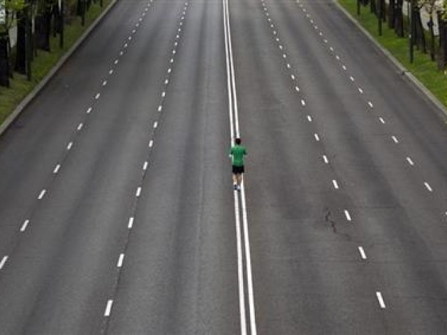 A runner warms up in the middle of an empty avenue. PHOTO: REUTERS