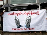journalists-hold-a-banner-as-they-protest-against-a-law-they-say-curbs-free-speech-at-the-start-of-a-trial-of-two-journalists-who-the-army-is-suing-for-defamation-over-a-satirical-article-in-yangon