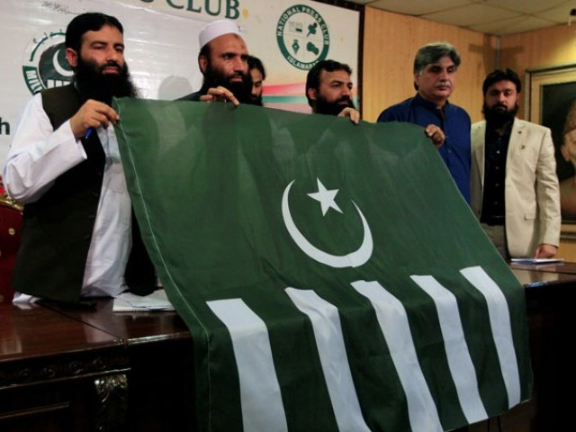 Saifullah Khalid (2nd L), president of Milli Muslim League (MML) political party, holds a party flag with others during a news conference in Islamabad on August 7, 2017. PHOTO: REUTERS