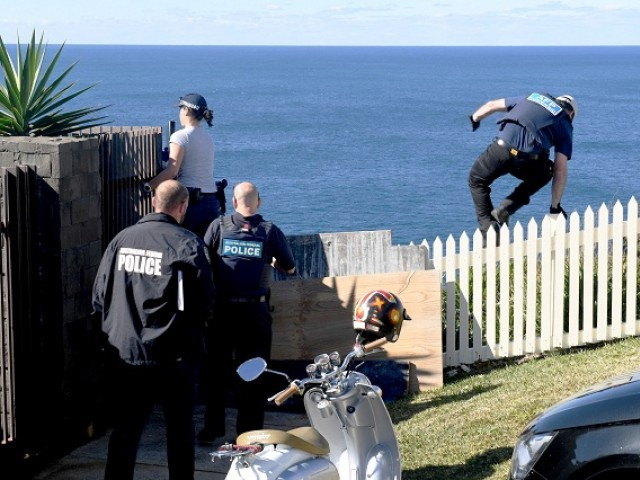 A policeman jumps a fence at the home of John Ibrahim during a police operation in Sydney, Australia, August 8, 2017 PHOTO: REUTERS