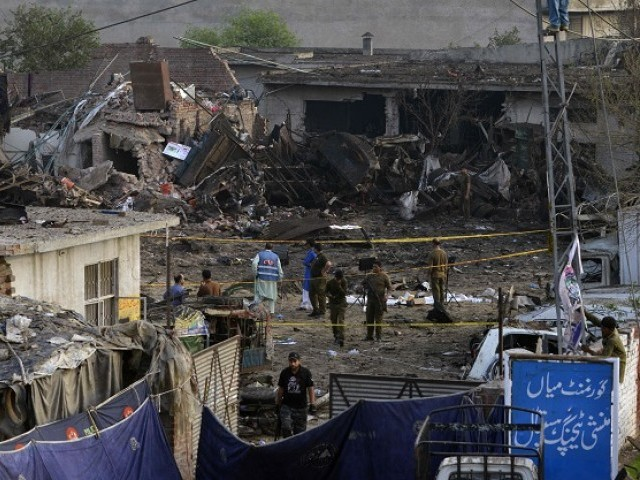 Security officials investigate the site following an overnight bomb explosion placed inside a truck in Lahore on August 8, 2017.