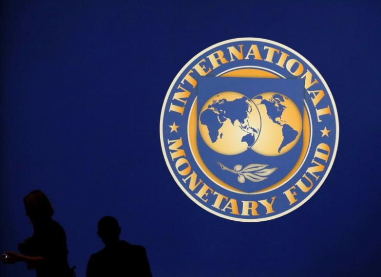 visitors-are-silhouetted-against-the-logo-of-the-international-monetary-fund-imf-in-tokyo-3-2-2