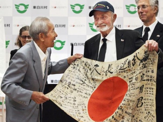 US World War Two veteran Marvin Strombo (C) meets with Tatsuya Yasue (L), brother of Sadao Yasue, to hand over a Japanese flag Strombo found in a battlefield in 1944, in Higashi-Shirakawa Village, Japan, in this photo taken by Kyodo August 15, 2017. PHOTO: REUTERS