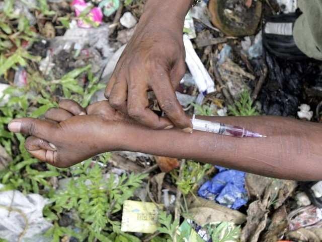 An injecting drug user injects himself with Fortwin on a roadside. PHOTO: REUTERS