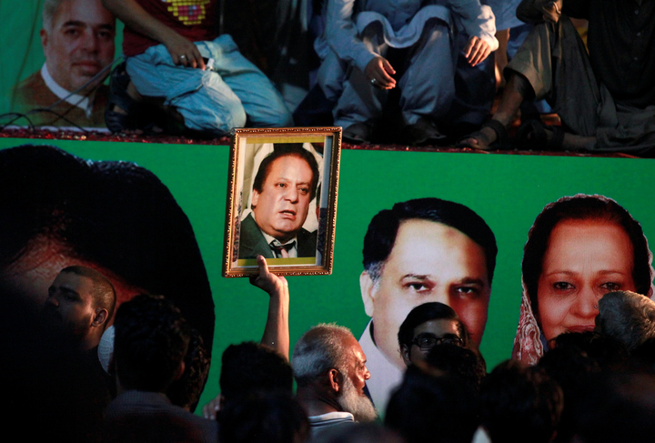 A supporter of former Pakistani prime minister Nawaz Sharif holds his picture as he waits for his convoy to pass through in Rawalpindi, Pakistan August 10, 2017. PHOTO: REUTERS
