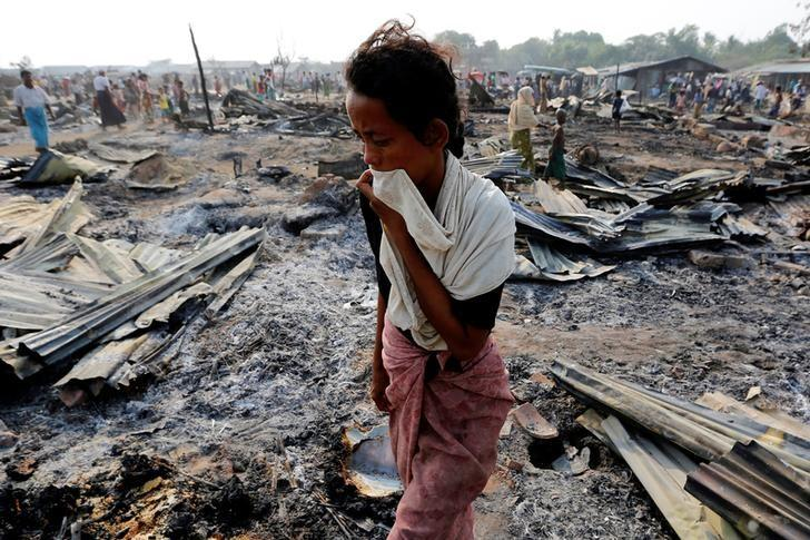A woman walks among debris after fire destroyed shelters at a camp for internally displaced Rohingya Muslims in the western Rakhine State near Sittwe, Myanmar. PHOTO: REUTERS
