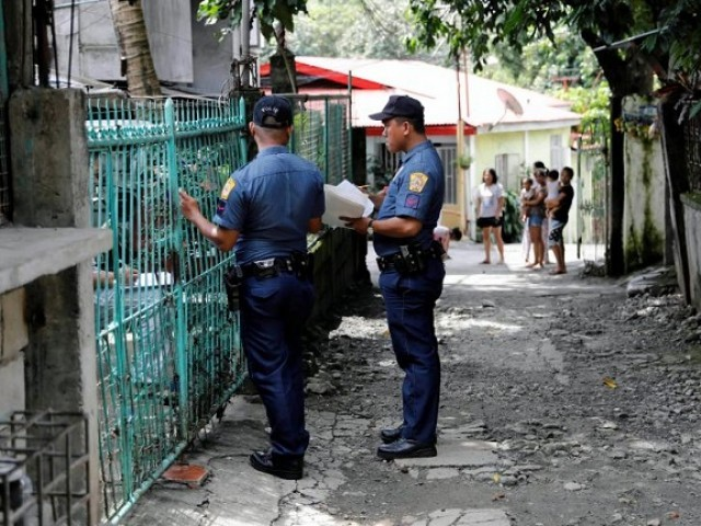 Policemen knock door to door and interview residents during a drug testing operation in Payatas, Quezon City, Metro Manila, Philippines August 23, 2017. PHOTO: REUTERS/Dondi Tawatao