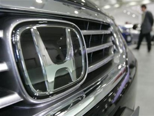 A man walks past Honda Motor Co. cars at a showroom in Tokyo January 30, 2008. PHOTO: REUTERS