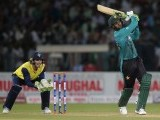 Pakistani batsman Shoaib Malik (R) hits a six as World XI wicketkeeper Tim Paine looks on during the second Twenty20 International match between the World XI and Pakistan at the Gaddafi Cricket Stadium in Lahore on September 13, 2017.  PHOTO: AFP
