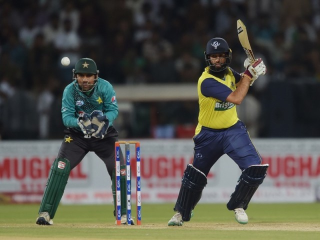World XI batsman Hashim Amla (R) plays a shot as Pakistani captain and wicketkeeper Sarfraz Ahmad looks on during the second Twenty20 International match between the World XI and Pakistan at the Gaddafi Cricket Stadium in Lahore on September 13, 2017. PHOTO: AFP