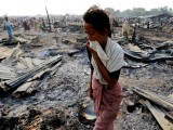a-woman-walks-among-debris-after-fire-destroyed-shelters-at-a-camp-for-internally-displaced-rohingya-muslims-in-the-western-rakhine-state-near-sittwe-4-2-2-2-2