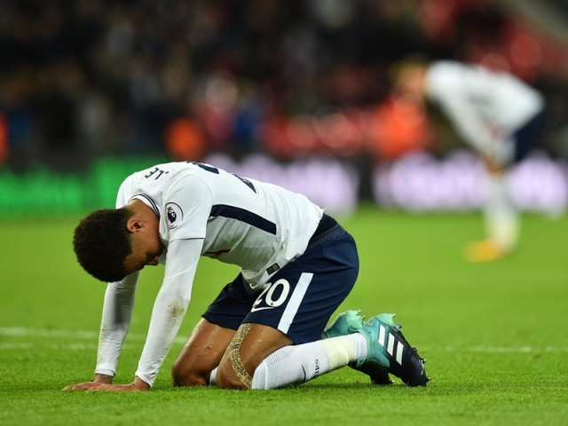 Tottenham Hotspur's English midfielder Dele Alli sinks to his knees at the final whistle in the English Premier League football match between Tottenham Hotspur and Swansea City at Wembley Stadium in London