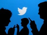 file-photo-people-holding-mobile-phones-are-silhouetted-against-a-backdrop-projected-with-the-twitter-logo-2