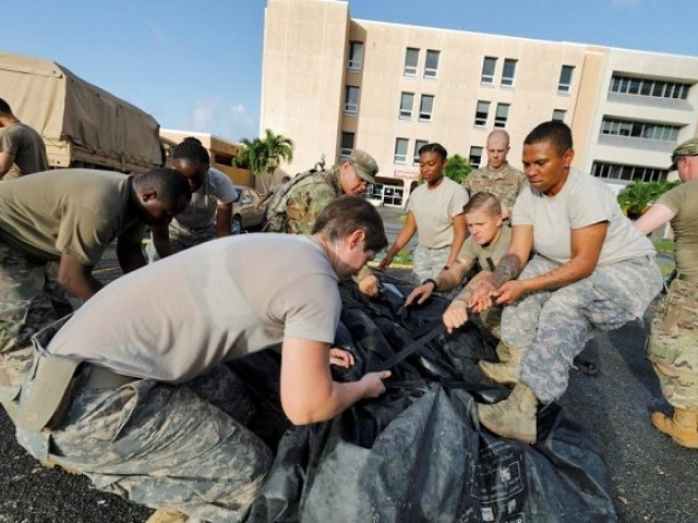 Soldiers from the 602nd Area Support Medical Company secure a portable tent as they break down a field hospital outside the Schneider Regional Medical Center while preparing to evacuate their unit in advance of Hurricane Maria, in Charlotte Amalie, St. Thomas, U.S. Virgin Islands September 17, 2017.  PHOTO: REUTERS/Jonathan Drake