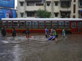 people-wade-through-a-water-logged-road-past-a-stalled-passenger-bus-during-rains-in-mumbai