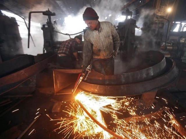 A worker cuts a steel rod inside a steel factory. PHOTO: REUTERS