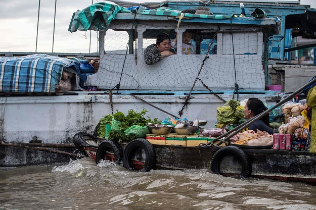 A boat vendor offers her vegetables to a house boat resident in a canal off the Song Hau river in the floating Cai Rang market in Can Tho, a small city of the Mekong Delta. PHOTO: AFP