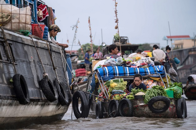 A vendor (R) prepares vegetables that she sold to a resident of a house boat in a canal off the Song Hau river in the floating Cai Rang market in Can Tho, a small city of the Mekong Delta. PHOTO: AFP