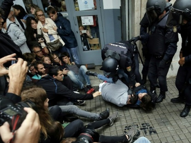 Spanish police immobilize two people outside a polling station in Barcelona as Catalonia holds an independence referendum banned by Madrid. PHOTO: AFP