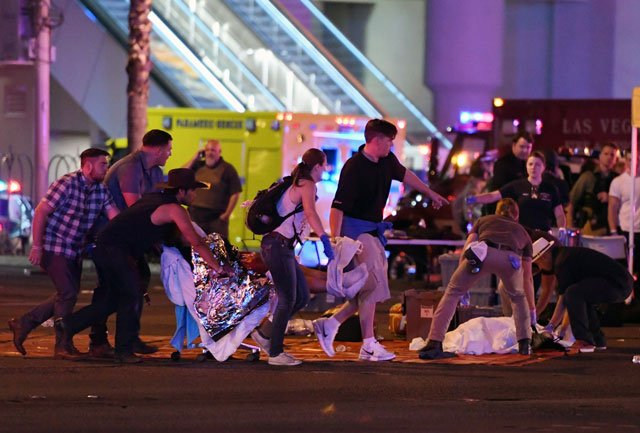 An injured person is tended to in the intersection of Tropicana Ave. and Las Vegas Boulevard after a mass shooting at a country music festival nearby on October 2, 2017 in Las Vegas, Nevada. PHOTO: AFP