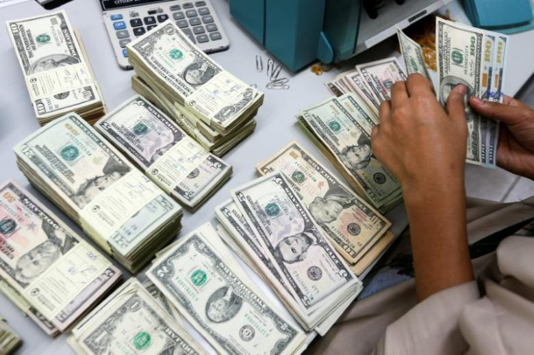 A bank employee counts U.S. dollar. PHOTO: REUTERS
