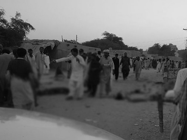 Devotees gather around the bodies of blast victims after a suicide bombing near a sufi shrine in the Gandawa area of Jhal Magsi district of Balochistan