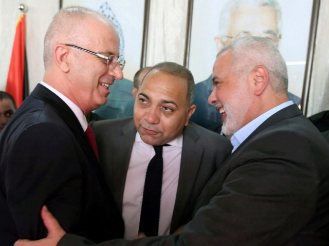 Prime Minister Rami Hamdallah shakes hands with Hamas chief Ismail Haniyeh in Gaza City on October 2