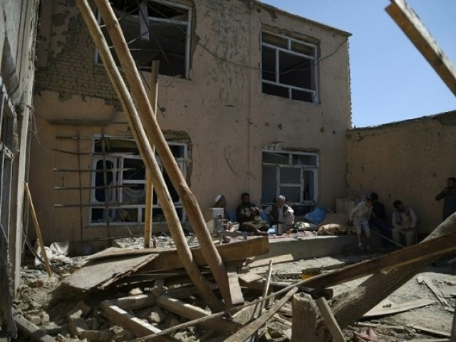 Afghan residents sit in a damaged courtyard as they drink tea following a US airstrike on a house in Kabul on September 28, 2017. PHOTO: YAHOO NEWS