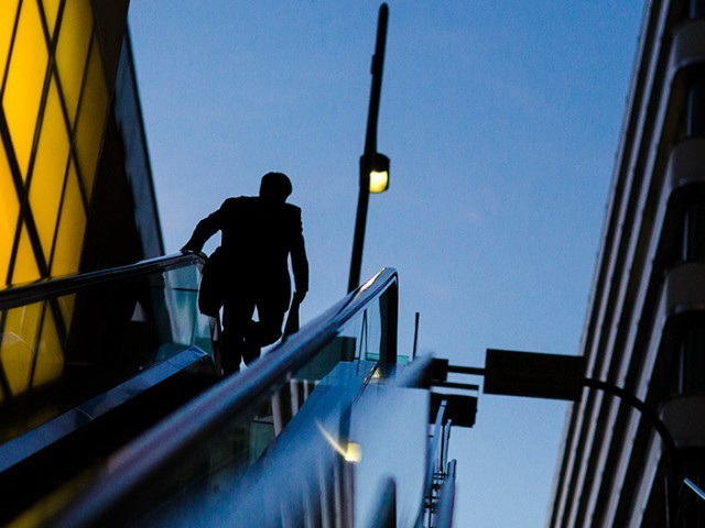 A businessman rides an escalator at a banking district. PHOTO: REUTERS