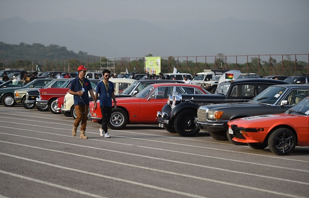 Participants walk past cars at the end of Motor Rally in Islamabad. PHOTO: AFP