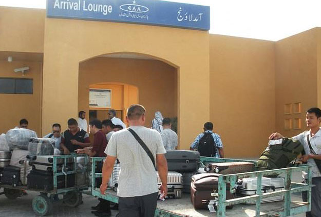 Chinese nationals wait to receive luggage after arriving at Gwadar Port. PHOTO: AFP