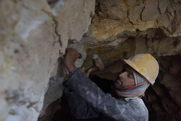 a Pakistani labourer Muhammad Azeem removing pieces of rock after blasting at a mountain to find gemstones in the Kashmiri town of Chitta Katha in Upper Neelum Valley. PHOTO: AFP