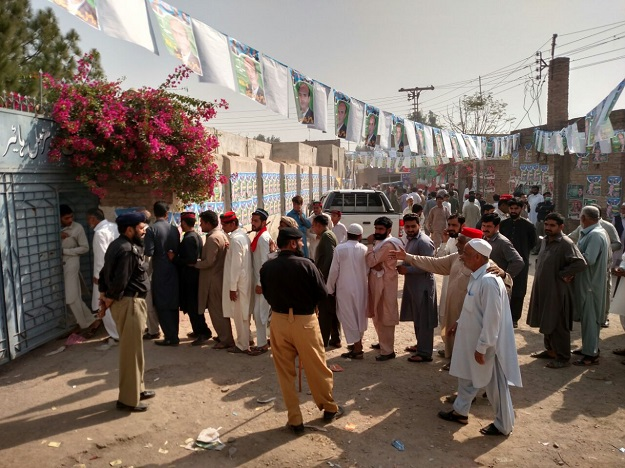 Male polling station of Government Shaheed Muzamil Higher Secondary School Chamkani. Police searching voter for cell phones as cell phones have been banned in the premises of all polling stations PHOTO: EXPRESS