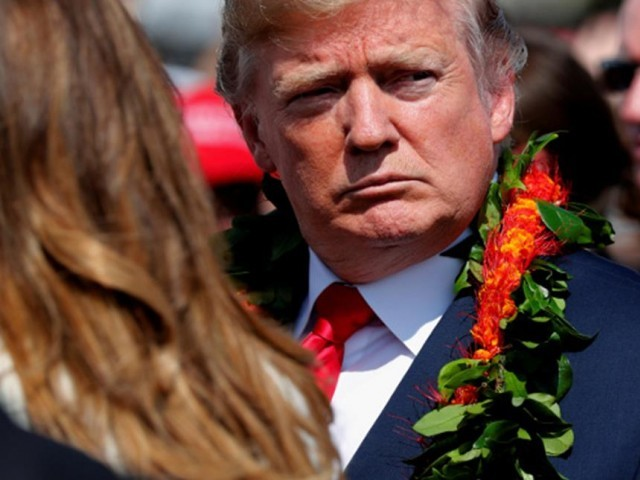 US President Donald Trump sports a flower lei he was given as he and first lady Melania Trump arrive aboard Air Force One at Hickam Air Force Base. PHOTO: REUTERS