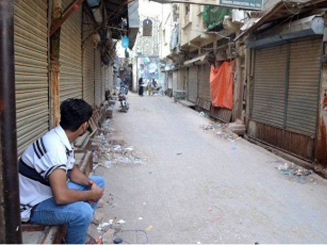 CLOSED FOR BUSINESS: A young man sits outside a closed wholesale drugs and chemist market after the market was sealed in raids on medical stores due to alleged sale of expired drugs in Hyderabad. PHOTO: ONLINE