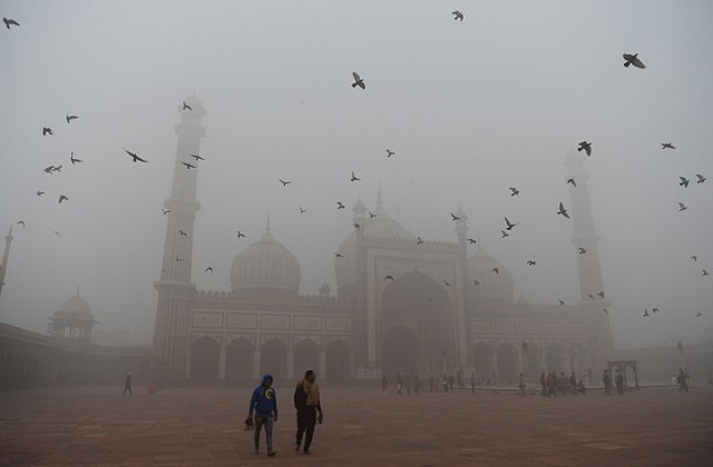 Visitors walk through the courtyard of Jama Masjid amid heavy smog in the old quarters of New Delhi.  PHOTO: AFP