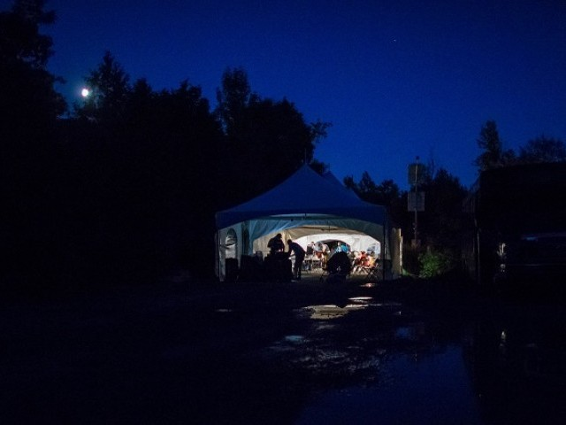 This file photo taken on August 05, 2017 shows refugees who crossed the Canada/US border illegally near Hemmingford, Quebec as they are processed in a tent after being arrested by the RCMP.  PHOTO: AFP