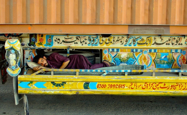 A labourer naps beneath a truck. The Super Highway was blocked by protesters on Sunday, causing a massive traffic jam. PHOTO: INP