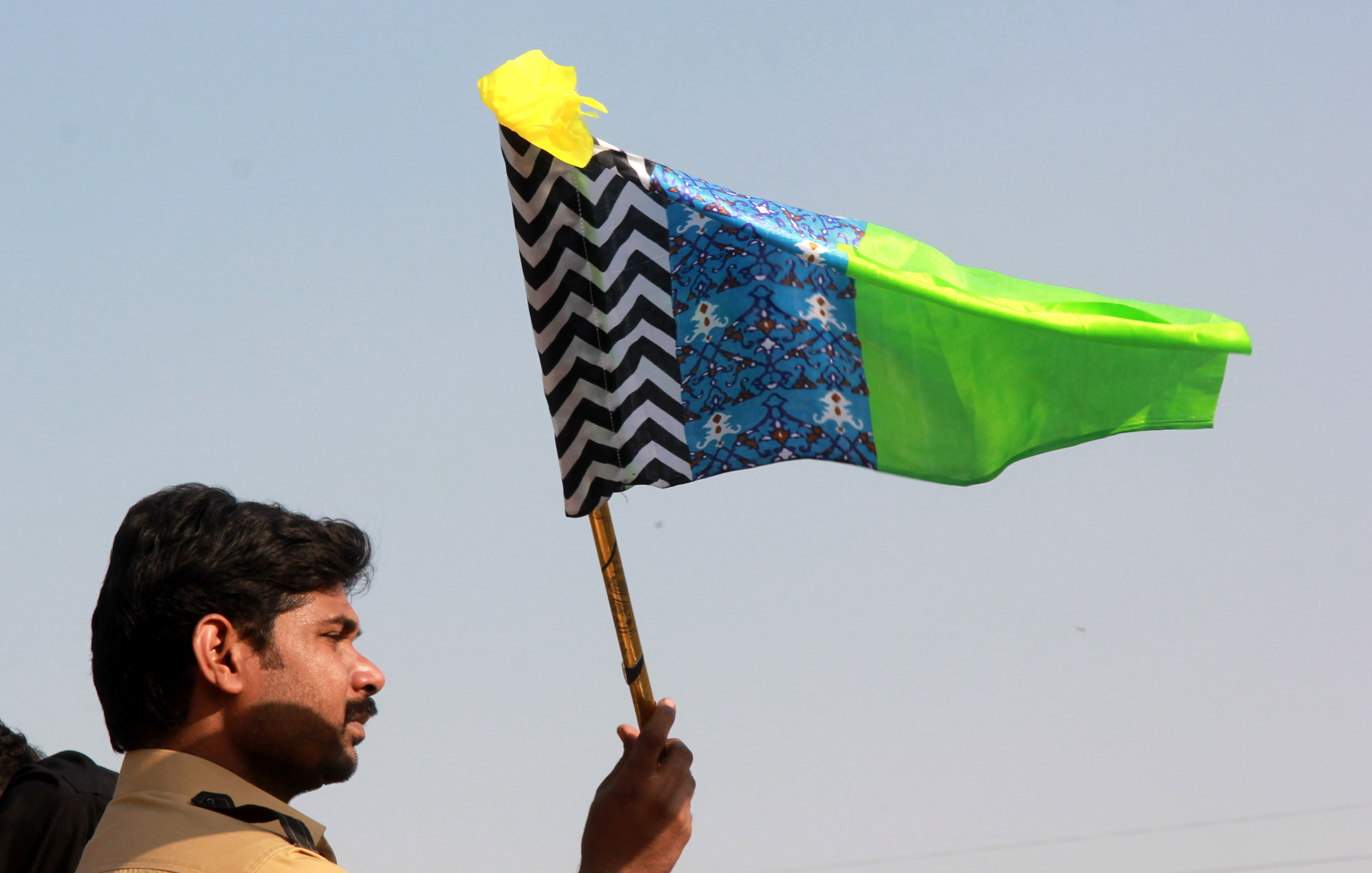 A supporter waves a flag at the protest at Numaish Chowrangi. PHOTO: ATHAR KHAN/EXPRESS