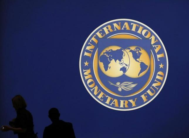 visitors-are-silhouetted-against-the-logo-of-the-international-monetary-fund-imf-in-tokyo-2-2-2